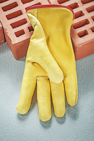 Red construction bricks leather protective gloves on concrete surface building concept. Stock Photo