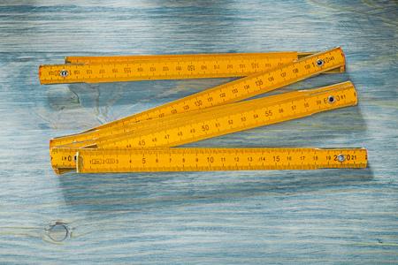 metro de medir: Wooden meter on vintage wood board construction concept. Foto de archivo