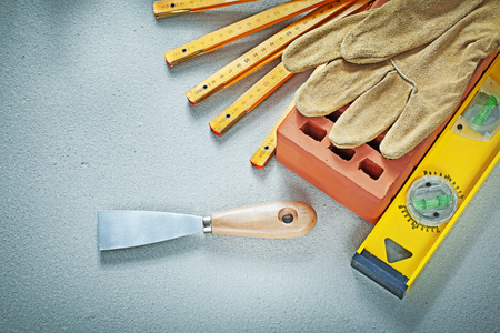 Red brick protective gloves palette knife construction level on concrete background bricklaying concept. Stock Photo