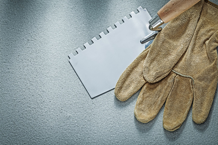 Paint scraper leather protective gloves on concrete background construction concept. Stock Photo