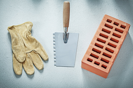 Orange bricks leather safety gloves putty knife on concrete background bricklaying concept. Imagens - 81914734
