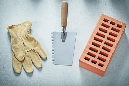 Oranje bakstenen lederen veiligheid handschoenen putty mes op concrete achtergrond metselen concept.