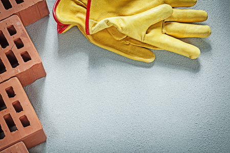 Set of orange construction bricks leather safety gloves on concrete background building concept. Stock Photo