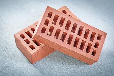 Red bricks on concrete background bricklaying concept.