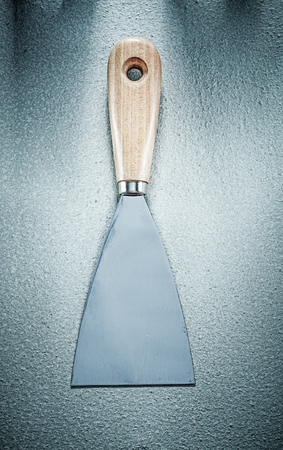Putty knife on concrete background construction concept.