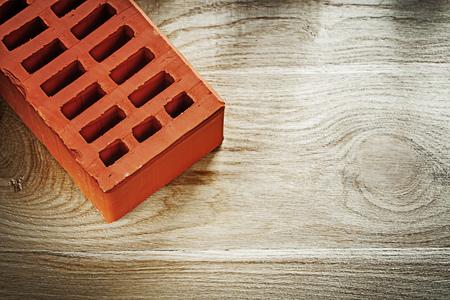 Orange building brick on wooden board construction concept.