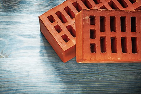 Set of red bricks on wood board construction concept.