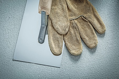Stainless putty knife leather protective glove on concrete background construction concept.