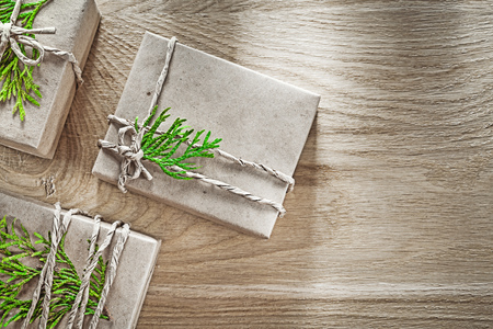 Wrapped handmade gift boxes with green branch holidays concept.