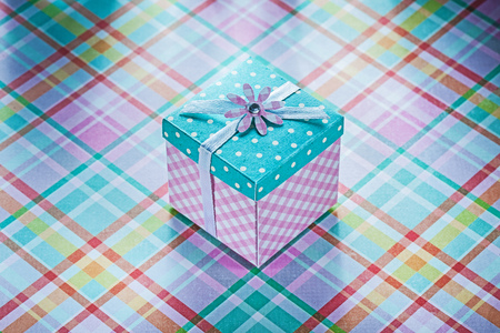 Wrapped present box on checked fabric background celebrations concept.
