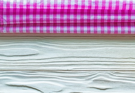 Pink squared cotton tablecloth on wooden board.
