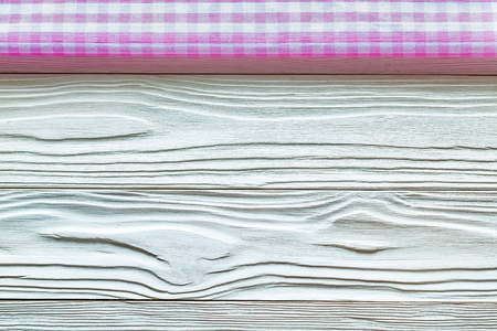 Pink checked table cloth on wooden board.