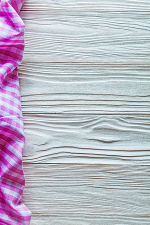 Pink cotton tablecloth on wooden board.