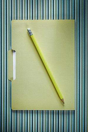stripy: Office folder pencil on stripy background directly above.