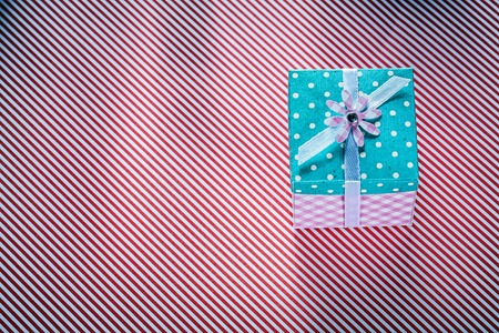 Packed present box on stripy fabric background celebrations concept.