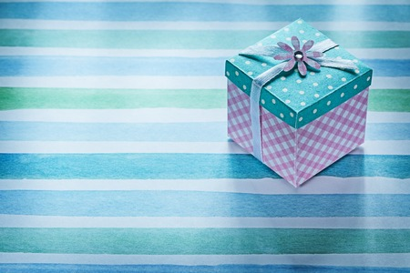 stripy: Packed gift box on blue striped fabric holidays concept.