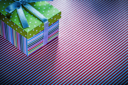 Gift box on red striped table cloth celebrations concept.