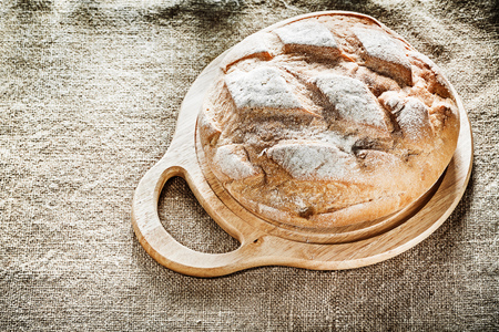 Chopping board bread on burlap background. Stock Photo