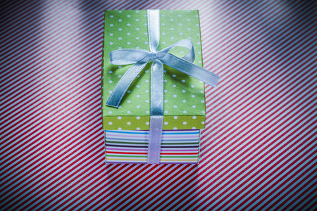 Present box on red striped fabric top view celebrations concept.