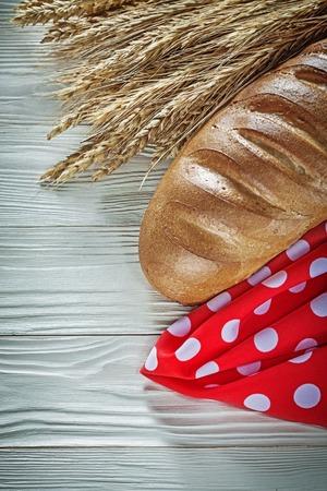 Bread stick wheat ears red napkin on white board. Stock Photo