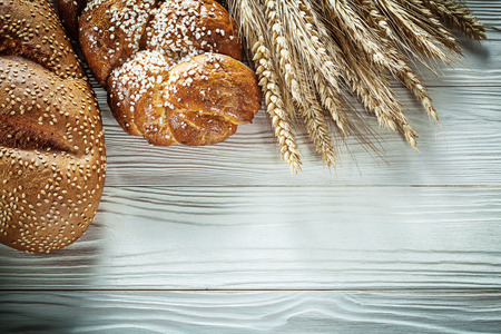 Loaf of bread wheat ears on white board. Stock Photo