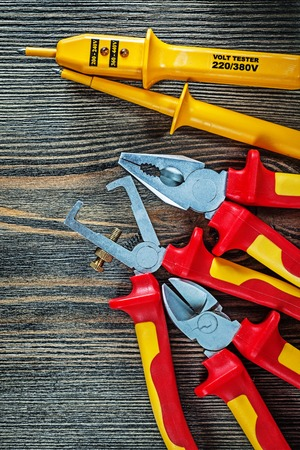 Electric tester insulated wire strippers cutting nippers pliers on wood board. Stock Photo