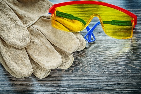Safety gloves goggles on wooden board. Stock Photo