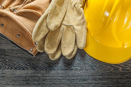 Leather tool belt protective gloves hard hat on black board.