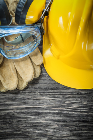 Protective gloves goggles earmuffs hard hat on wooden board. Stock Photo