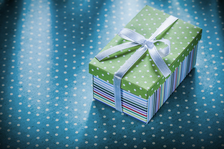 Gift box with ribbon on blue polka-dot tablecloth holidays concept.