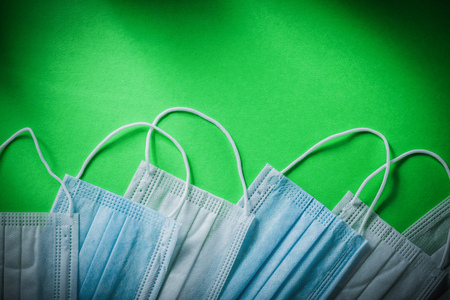 Disposable respiratory face masks on green background medicine concept.