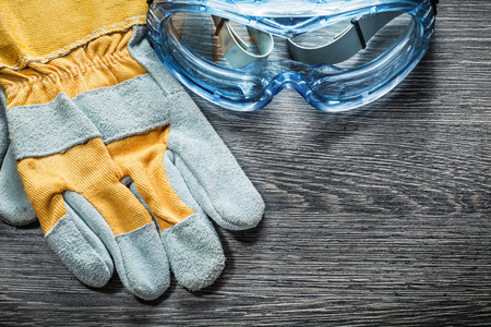 Protective gloves safety glasses on wooden board. Stock Photo