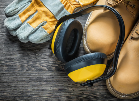 Safety gloves waterproof working boots earmuffs on wooden board. Stock Photo