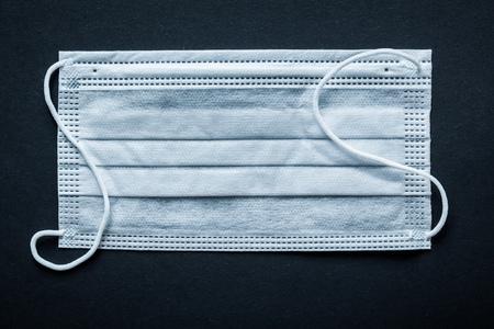utiles de aseo personal: Disposable face mask on black background. Foto de archivo