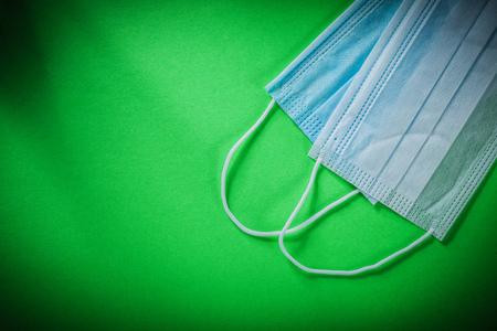 utiles de aseo personal: Máscara quirúrgica estéril disponible en fondo verde.