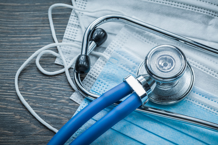 Disposable surgical masks stethoscope on wooden board.