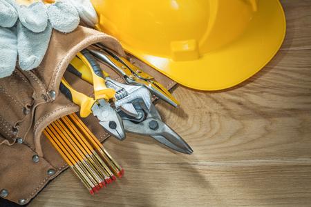 Building helmet safety gloves tool belt tooling on wooden board.