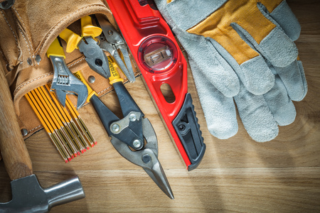 Tool belt with tooling construction level protective gloves on wooden board. Stock Photo