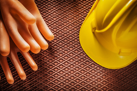Protective insulating gloves building helmet on dielectric rubber mat.