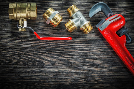 Plumbing pipe wrench connectors water valve on vintage wooden board. Stock Photo