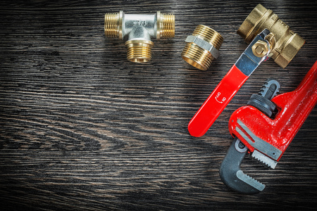 Plumbing monkey wrench connectors water valve on vintage wooden board.