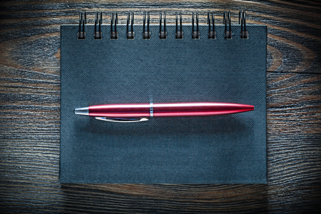 Black notebook pen on vintage wooden board top view. Stock Photo
