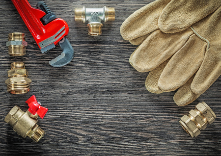 Safety gloves plumbing pipe wrench connectors water valve on wooden board.