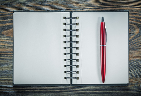 Blank spiral notebook pen on vintage wooden board. Stock Photo