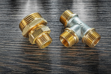 T-tube pipe connector threaded fitting on vintage wooden board. Stock Photo