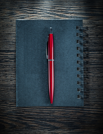 Black notepad ballpoint pen on vintage wooden board. Stock Photo