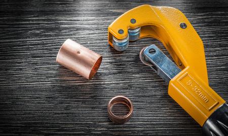 Coupe-pipe en cuivre sur planche de bois. Banque d'images