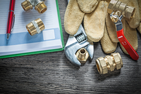 Adjustable spanner plumbing pipe connectors leather protective gloves water valve notebook pen. Stock Photo