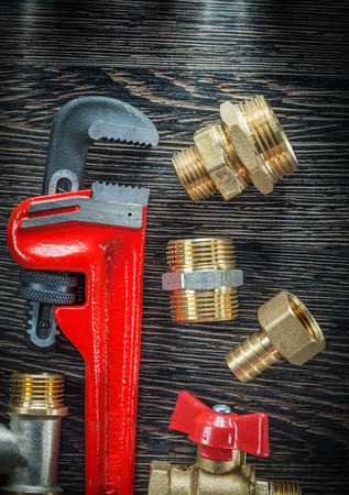 Plumbing adjustable wrench threaded pipe fittings water valve on wooden board.