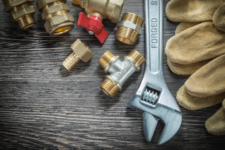 Adjustable wrench water valve pipe fittings safety gloves on wooden board. Stok Fotoğraf